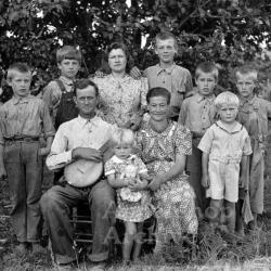 Exterior portrait of large family, man holding banjo