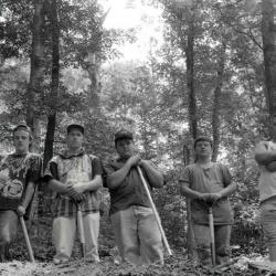 Young men posing with shovels in forest setting